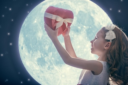 Sweet child girl with red heart. Happy little girl with gift box on background of the moon. Wedding, Valentine, celebration concept.